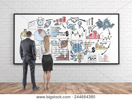 Rear View Of Young And Successful Business Partners Wearing Suits Looking At A Colorful Mind Map Of