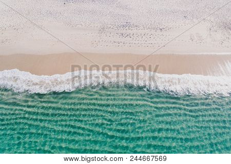 The Shore Of The Sea, Photographed With Great Height: Green Water With Waves, White Foam Near The Sh