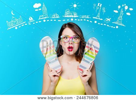 Portrait Of Beautiful Surprised Young Woman With Sandals On The Wonderful Blue Studio Background Wit