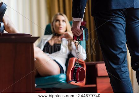 Sexy Bdsm Games Of Couple At Office Background. Woman On Chair And Man Holds Handcuffs.
