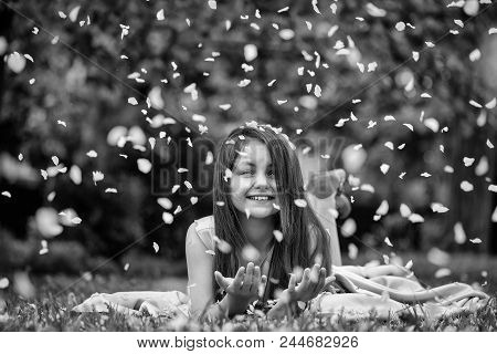 Happy Child And Flower Petals. Beautiful Little Girl In Pink Dress With Long Brunette Hair And Smili