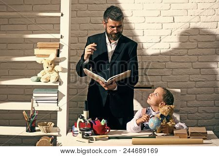 Education And Back To School Concept. Kid And Man By Desk With School Supplies. Schoolgirl And Tutor