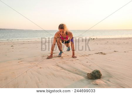 sportswoman in earphones with smartphone in armband case exercising on sandy beach with sea behind poster