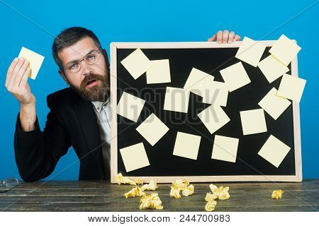 Handsome Bearded Man In Spectacles Holds Reminder Board. Sad Man In Casual Clothes Taking Notes On W