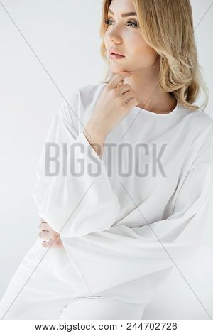 Portrait Of Beautiful Pensive Blond Woman In White Clothing Posing On White Background