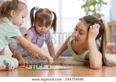Happy Family. Young Mother Playing Ludo Boardgame With Her Children Daughters While Spending Time To