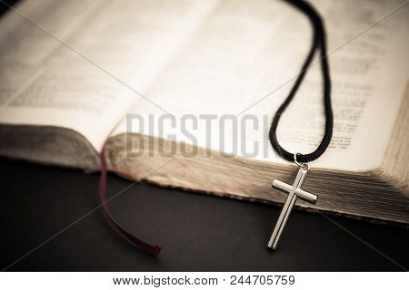 An Open Book With A Cross On A Dark Background