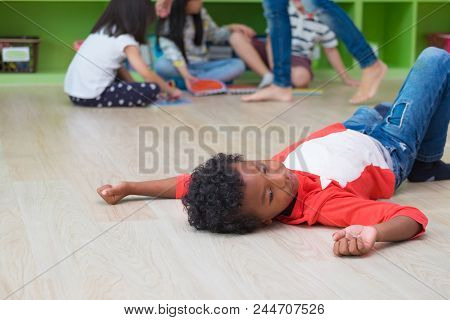 African American Kid With Loneliness Emotion Separate From Group Of Friends In Classroom In Kinderga