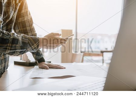 Man Standing And Message To Customer On Smartphone And Working In Modern Office.