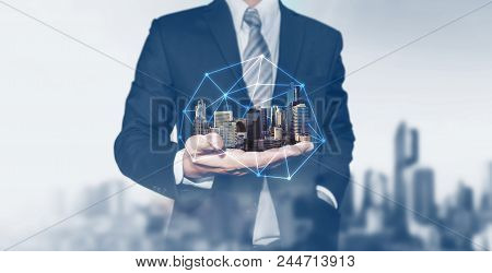 Building Technology And Business Real Estate Investment. Businessman Holding Buildings On Hand