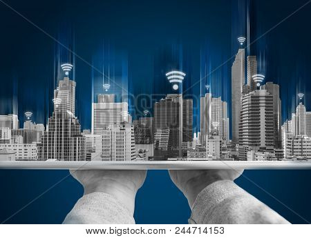 Wifi Network Connection And Smart City Concept. Hand Holding Digital Tablet And Building Hologram Wi
