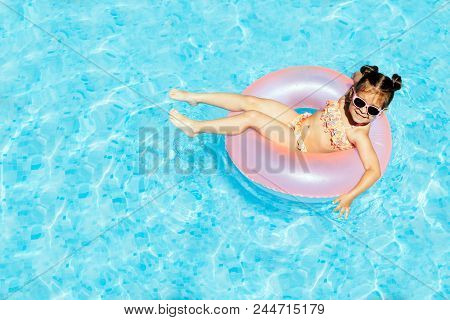 Cute And Funny Little Girl In Swimming Pool, Swimming In Pool Float Ring, Wearing Sun Glasses And Ha