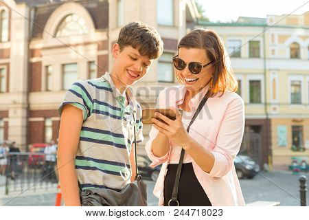 Parent And Teenager, Relationship. Mother And Son Teenage Are Looking At The Mobile Phone And Laughi