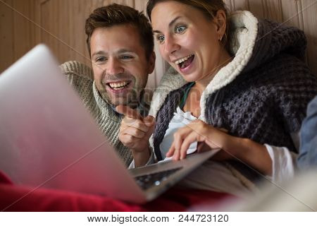 Happy European Family Making Shopping In Internet Using Laptop. Man And Woman Are Happy And Smiling