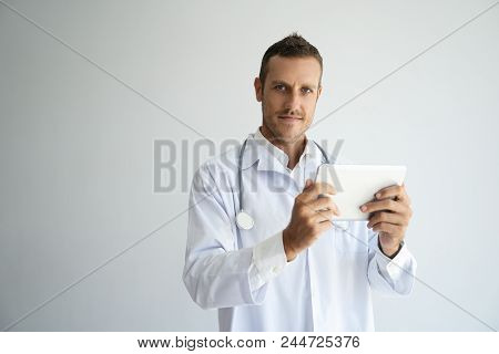 Focused Handsome Doctor Reviewing Patient Test Results. Young Practitioner In White Coat Using Table
