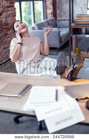 Great News. Vigorous Female Employee Putting Legs On Table And Talking On Phone