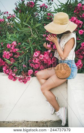 Young Blonde Slim Girl In Sunhat, Lace Top And Denim Shorts With Straw Round Bag Sitting On White Pa