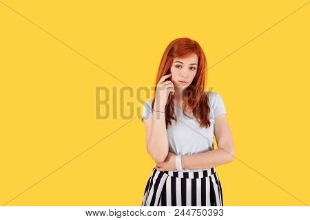 Pensive Look. Nice Thoughtful Woman Looking At You While Standing Against Yellow Background