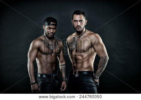 Machos With Muscular Tattooed Torsos Look Attractive, Dark Background. Guys Sportsmen With Sexy Musc