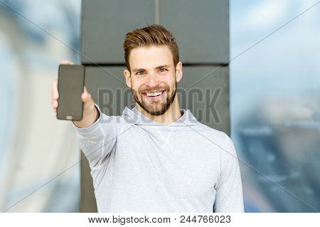 Showing His Brand New Smart Phone. Man Beard With Smartphone, Urban Background. Man With Beard Happy
