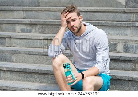 Working Out On Stairs. Man Athletic Appearance Exhausted Holds Water Bottle. Man Athlete Sport Cloth