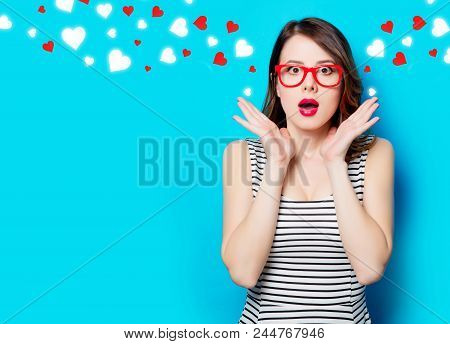 Portrait Of Beautiful Surprised Young Woman In Glasses On The Wonderful Blue Studio Background And A