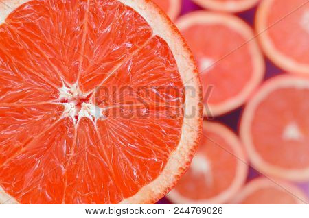 Top View Of A Fragment Of The Red Grapefruit Slice On The Background Of Many Blurred Grapefruit Slic