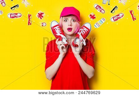 portrait of beautiful surprised young woman with red gumshoes on the wonderful yellow studio background and with clothes poster