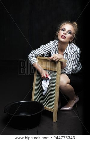 Woman Housewife Is Engaged In The Laundry. Annoyed Depressed Housewife Doing Laundry On Black Backgr