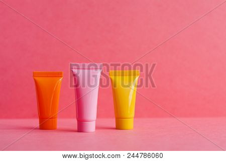 Three 3 Cosmetic Tubes On Pink Polka Dot Background. Blank Plastic Containers, Simple Packaging Desi
