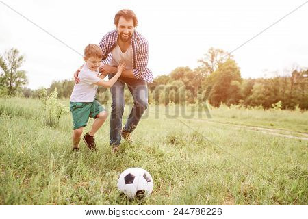 Father Is Playing Football With His Son. They Are Running Down The Meadow. Boy Is Hugging His Dad An
