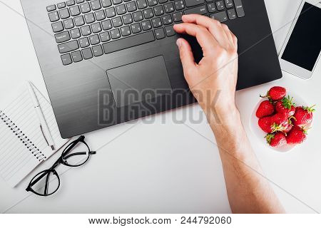 Top View Of Self-employed Man Working On Laptop With Notebook, Smartphone, Glasses And Snack On Desk