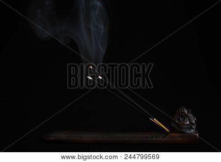 burning and smoking sandalwood sticks close-up on a dark background on a decorative stand with an oriental deity poster