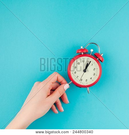Creative Flat Lay Concept Top View Of Woman Hand Holding The Red Vintage Alarm Clock On Square Brigh