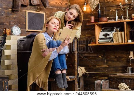 Mom And Daughter With Concentrated Look Reading Together, Home Education Concept. Beautiful Blond La
