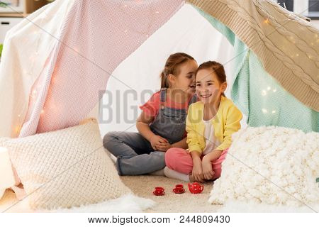 childhood and hygge concept - happy little girls playing tea party with toy crockery in kids tent at home and sharing secrets poster