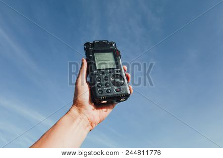portable audio recorder in hand recording ambient sounds of nature