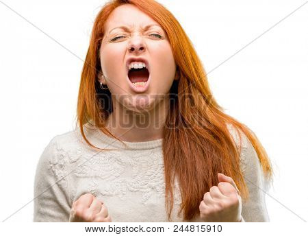 Beautiful young redhead woman happy and excited celebrating victory expressing big success, power, energy and positive emotions. Celebrates new job joyful isolated over white background