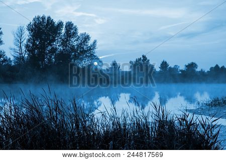 Sunrise scene with night mist over river in moonlight