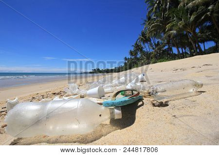 Plastic pollution on beach. Plastic water bottles, bags, shoes and other debris washed up on beach