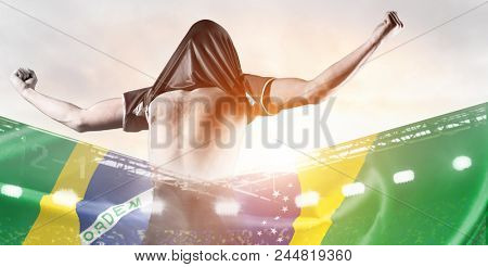 Brazil national team. Double exposure photo of stadium and soccer or football player celebrating goal with his jersey on head