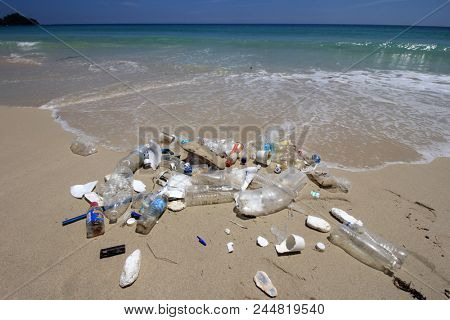 KUDAT, MALAYSIA - CIRCA JUNE 2018: Plastic bottles, bags and other garbage dumped on beach and swept into ocean. Environmental pollution problem.