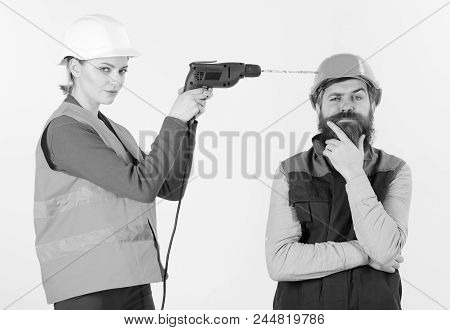 Woman Drills Head Of Man, White Background. Man In Helmet With Carefree Face Ignoring His Wife Drill
