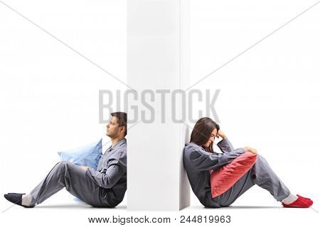 Young couple mad at each other sitting on opposite sides of a wall isolated on white background