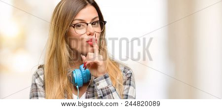 Young student woman with headphones and backpack with index finger on lips, ask to be quiet. Silence and secret concept