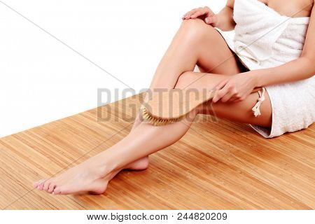 Woman is massaging skin on her legs with big brush, isolated on white background