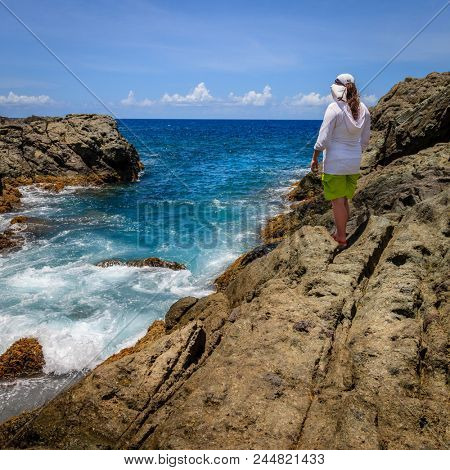 A woman standing on a cliff and watching surf on an island in BVI
