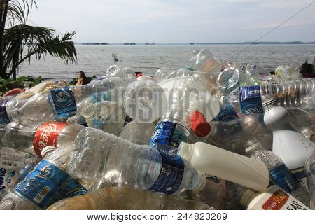 SANDAKAN, MALAYSIA - CIRCA JUNE 2018: Plastic pollution environmental problem. Single use plastic drinks bottles dumped on beach and in ocean