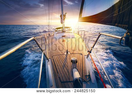 Sunset at the Sailboat deck while cruising / sailing at opened sea. Yacht with full sails up at the end of windy day. Sailing theme - background.