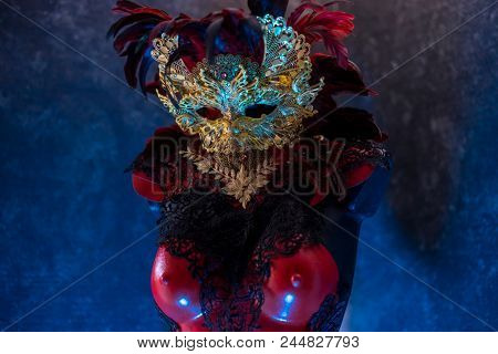 Red golden venetian carnival mask with feathers  on a draped red velvet theater curtain. Mask in the dark